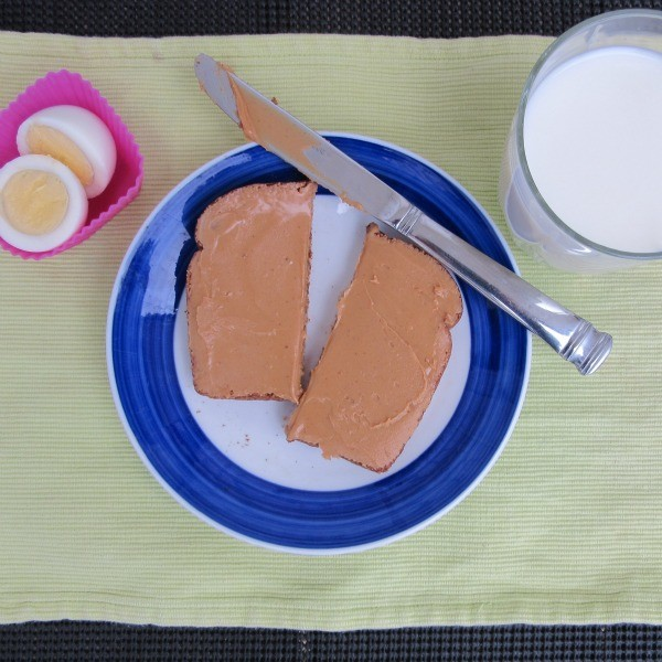 breakfast with peanut butter toast, a boiled egg, and milk